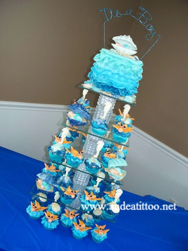 "It's a Boy, Baby Shower cupcake tower! This was a 6"" coconut cake filled with pineapple, chocolate cupcakes filled with strawberry and almond cupcakes filled with red raspberry, vanilla butter cream over all. All of the seashells, seahorses and the babies are white chocolate."